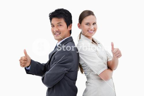 Business people standing back-to-back with the thumb up