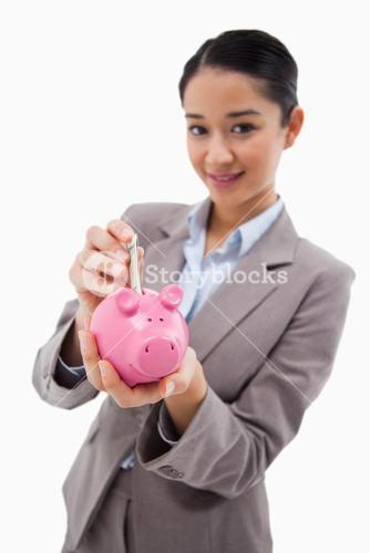 Portrait of a businesswoman putting a bank note in a piggy bank