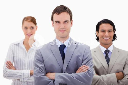 Smiling businesspeople with arms folded