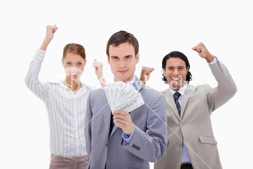 Businessman with cheering colleagues and money
