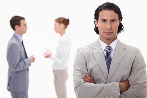 Serious businessman with talking colleagues behind him