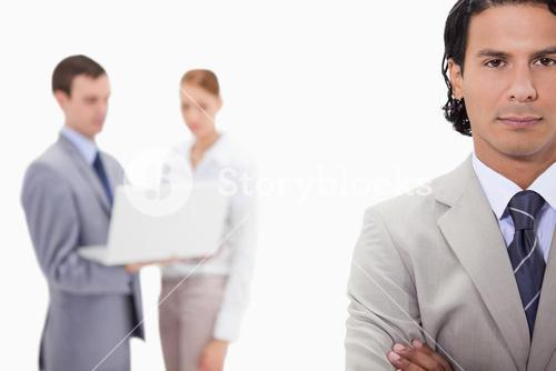 Businessman with colleagues with laptop behind him