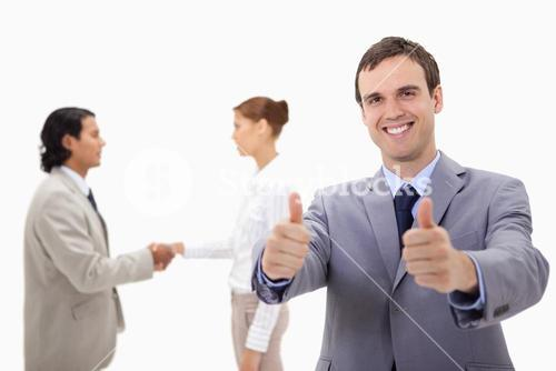 Businessman approving with hand shaking colleagues behind him