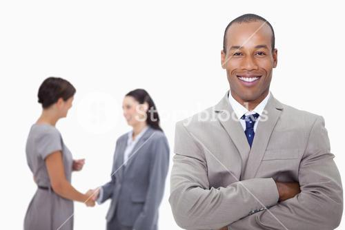 Smiling businessman with folded arms and colleagues behind him