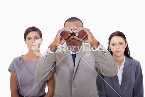 Businessman with colleagues using binoculars