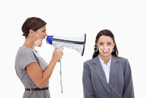 Businesswoman using megaphone to yell at colleague
