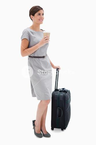 Side view of woman with coffee and wheely bag