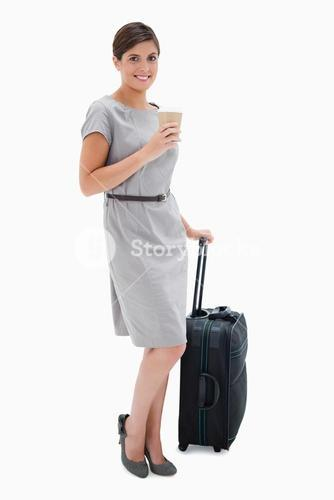 Smiling woman with coffee and wheely bag