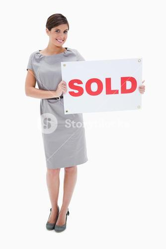 Woman holding sold sign in her hands