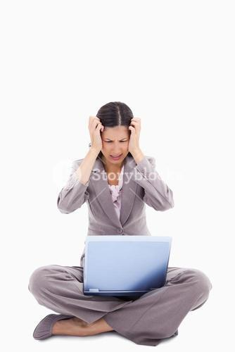 Sitting woman having trouble with notebook