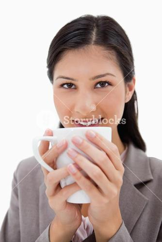 Businesswoman holding cup with both hands