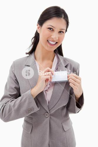 Smiling businesswoman putting on name badge