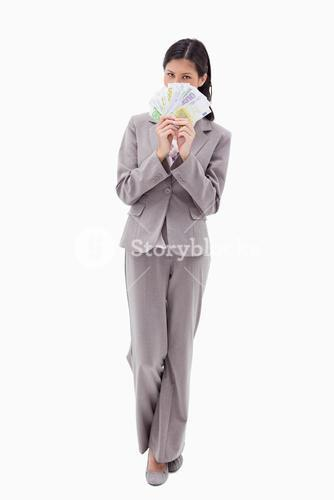 Businesswoman hiding face behind bank notes