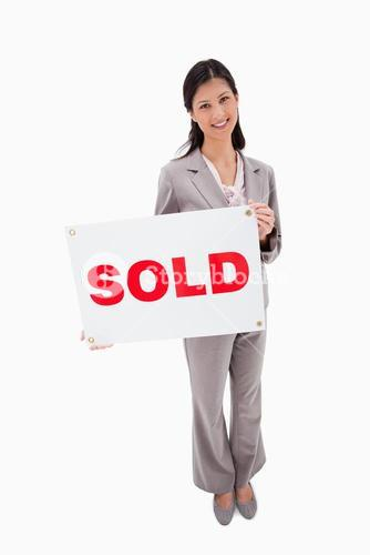 Real estate agent with sold sign