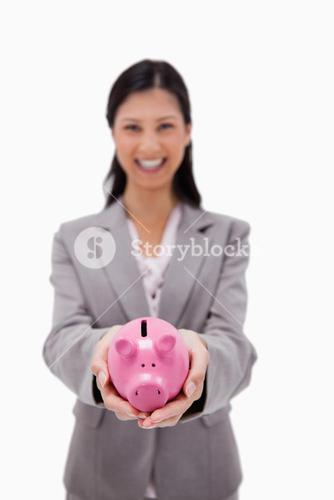 Piggy bank being held by businesswoman