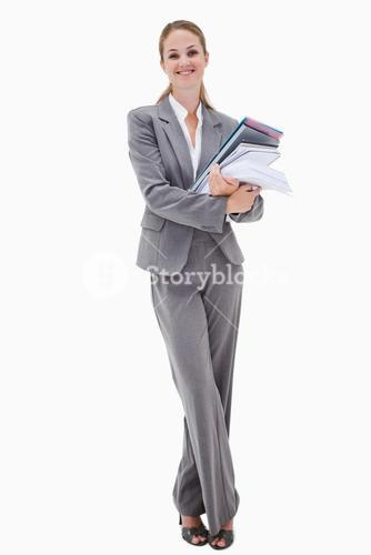 Smiling office employee with pile of paperwork