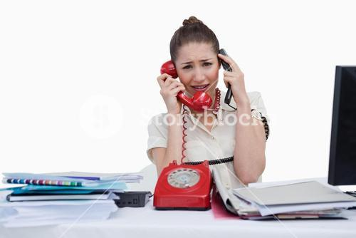 Overworked businesswoman answering the phones
