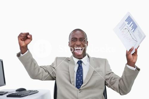 Victorious salesman with the fists up while holding a graph