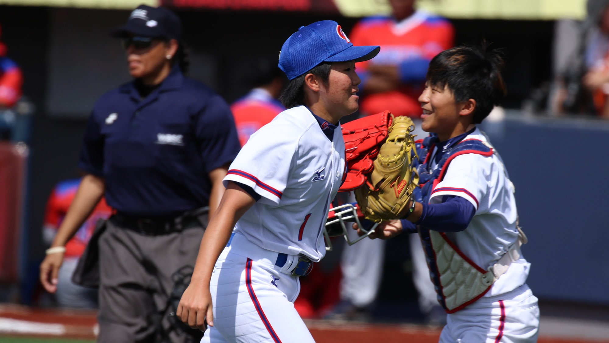 Hsieh Yu Ying congratulated by catcher Ying Lee Shih after getting out of the eighth without allowing a run