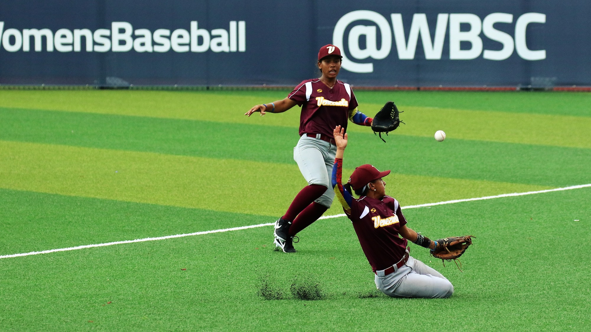Ingrid Escobar and Yusneiby Acacio chase a fly ball in foul territory