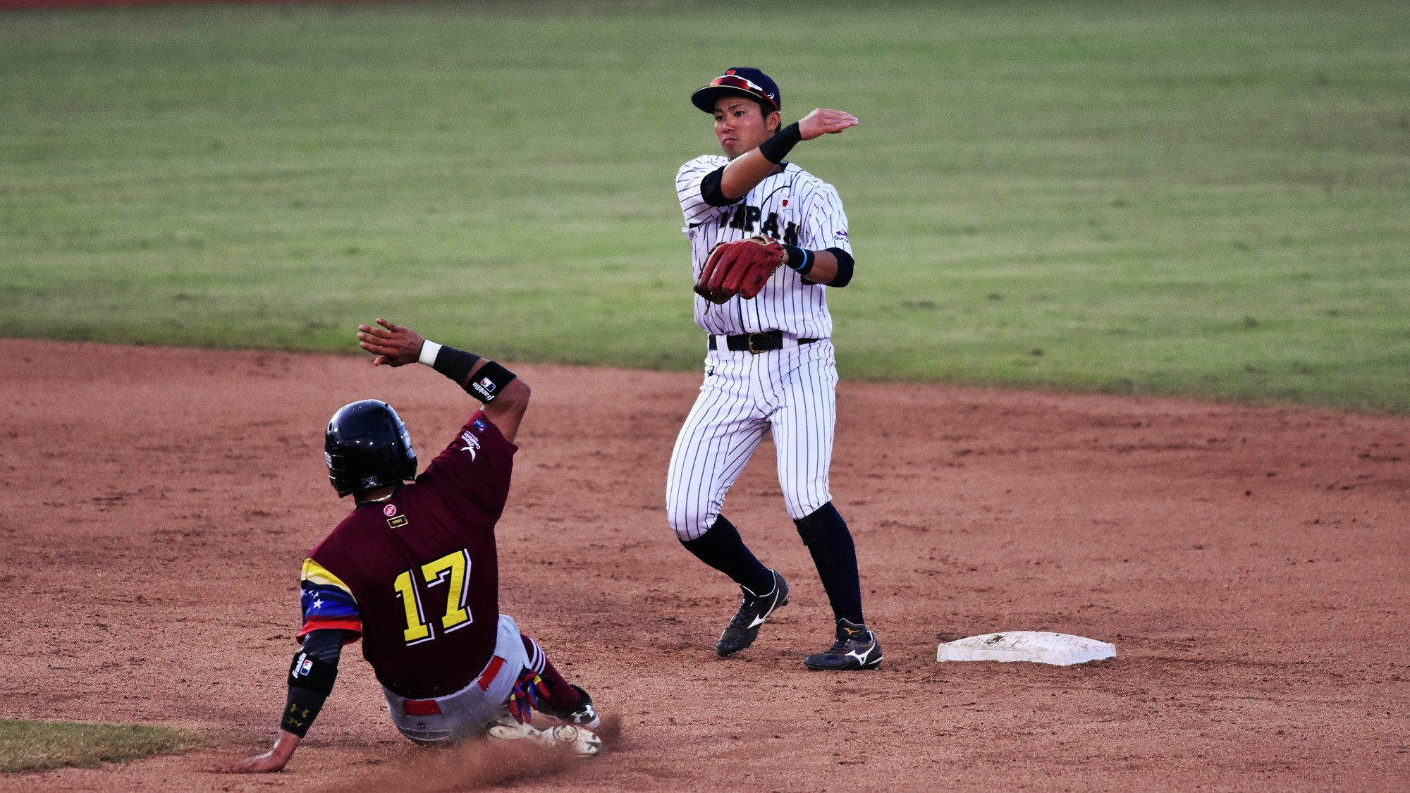 Japan's Taiga Matsuo turns a double play over Jorma Rodriguez of Venezuela
