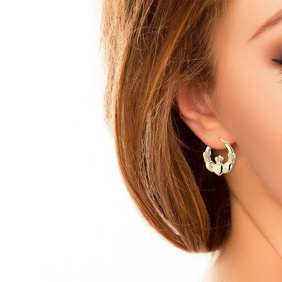 a model wearing Claddagh creole hooped earrings