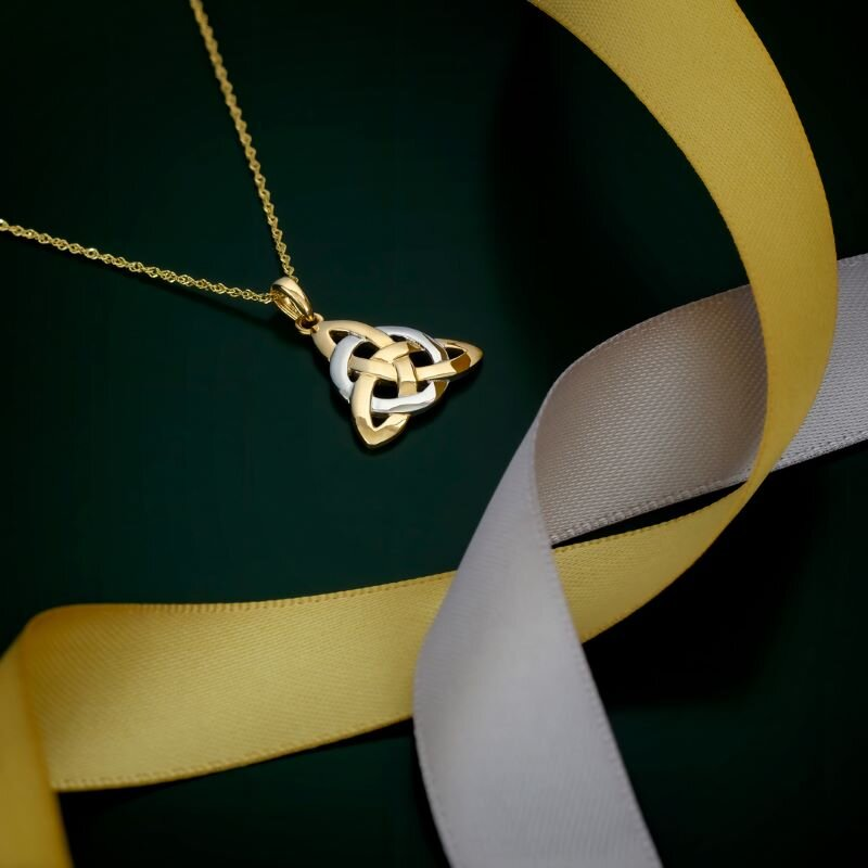 styled image of Solvar two tone gold celtic trinity knot necklace S44061 on green background