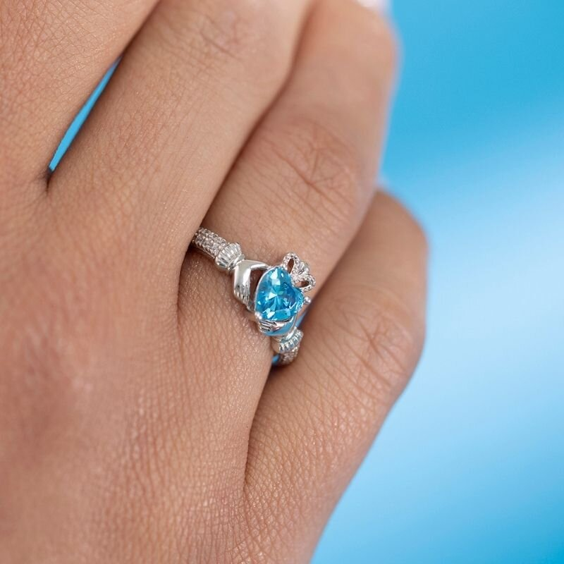 a model wearing Solvar march birthstone aquamarine claddagh ring