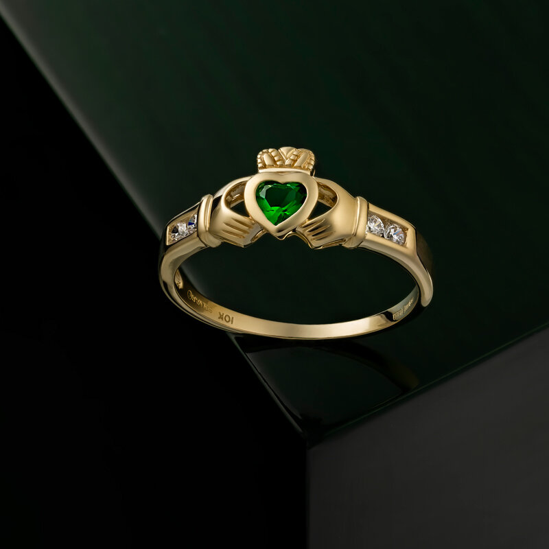 styled image of Solvar gold emerald claddagh ring S2518 on dark green background