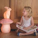 Child reading beside a large red toadstool lamp and a rabbit lamp