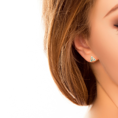 A model wearing Solvar 14 karat gold emerald trinity knot stud earrings