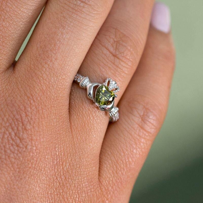 a model wearing Solvar august birthstone peridot claddagh ring