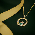 syled image of Solvar emerald and diamond claddagh pendant S46531 on green background