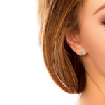 A model wearing Solvar 14 karat gold emerald trinity knot stud earrings