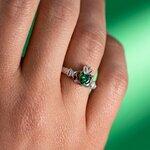 a model wearing  Solvar may birthstone emerald claddagh ring