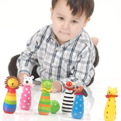 child playing with wooden animal skittles