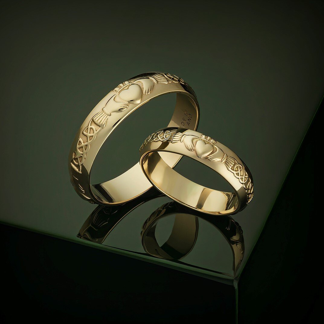 styled image of gold Solvar mens claddagh wedding band S2309 and matching ladies wedding band S2305