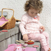 Child playing with the ladybug tea set in a wicker picnic basket