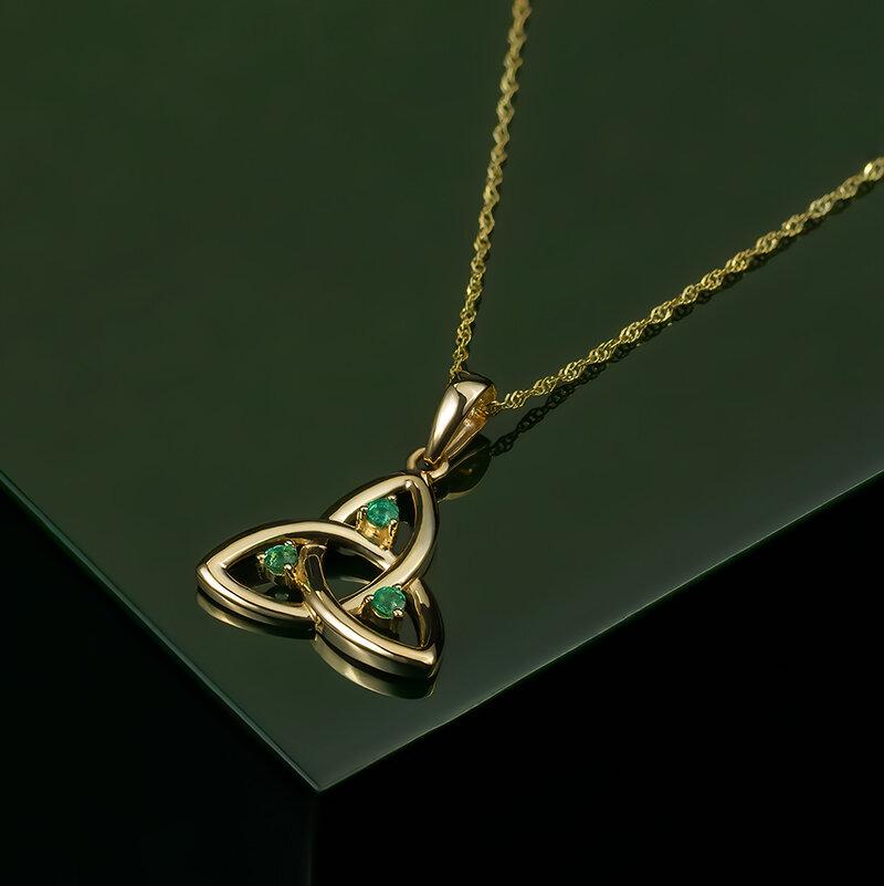 Styled image of Solvar 10 karat gold emerald Trinity Knot pendant S45717 on green background