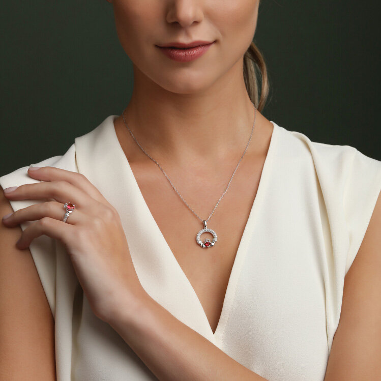 a model wearing Solvar january birthstone garnet claddagh necklace and ring