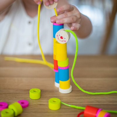 child playing with caterpillar threading toy