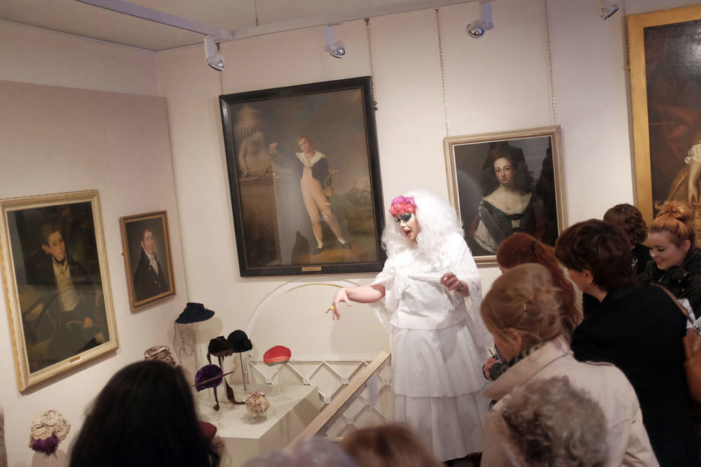 A drag queen giving a tour of a museum costume collection.