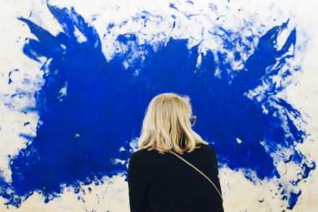 Woman Standing In Front Of Wall With Splash Of Paint