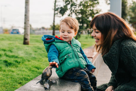 Boy And Mother Looking At Small Public Art Sculpture Of Bird
