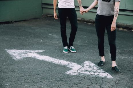 Couple Holding Hands In Front Of Road Markings