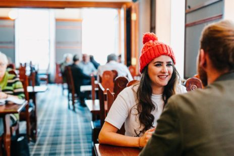 Girl In Red Hat Chatting With Man In Cafe