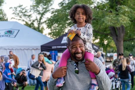Man Carrying Daughter On Shoulders At Festival