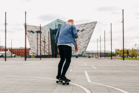 Man Skateboarding In Front Of Titanic Building