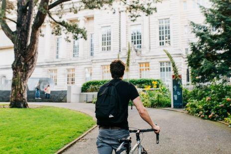 Man Walking Bike Towards Museum Building