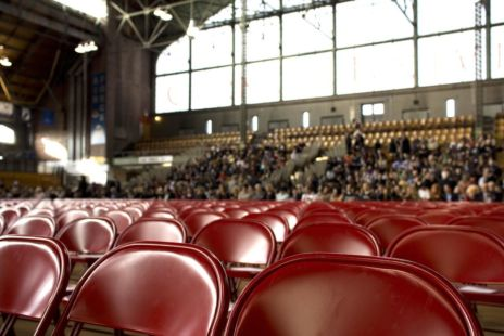 Red Seats In A Large Auditorium With Audience In Background